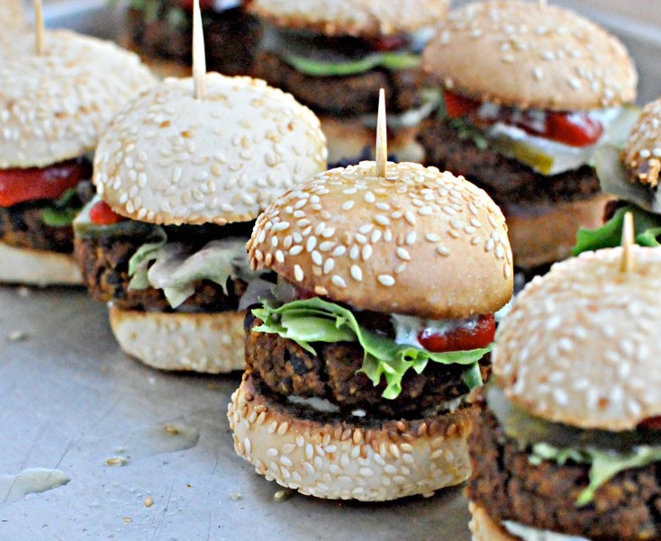 Mini veggie burgers with rocket salsa, avocado and melted cheese